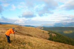 Photographer and autumn mountains Stock Photo
