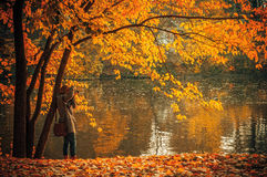 Photographer on autumn waterfront Stock Photos