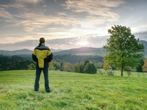 Photographer on autumnal meadow is waiting for sunrise. The man photographer with a photocamera on a tripod Royalty Free Stock Image
