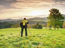 Photographer on autumnal meadow is waiting for sunrise. The man photographer with a photocamera on a tripod Royalty Free Stock Photo
