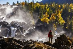 Photographer with backpack enjoying amazing waterfall Travel Lifestyle and success concept vacations into the wild royalty free stock image