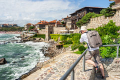 Photographer with backpack shooting in old town Sozopol near sea royalty free stock images