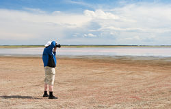 The photographer on bank salty lake Royalty Free Stock Photo