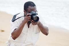 Photographer at the beach. This gentleman is taking pictures to his friends at the beach Stock Image