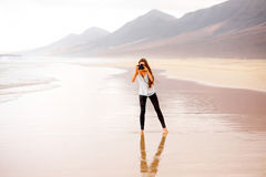 Photographer on the beach. Young female photographer photographing with professional camerastanding on the sandy beach with mountains on the background Royalty Free Stock Image