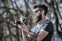 Photographer with beard and mustache amateur photographer nature background. Man with long beard busy with shooting. Photos. Photographer concept. Man bearded stock photos