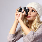 Photographer. Beautiful blonde young woman taking photo. With vintage camera in studio Stock Photos