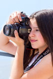 Photographer. Beautiful young girl taking pictures with a digital camera stock images