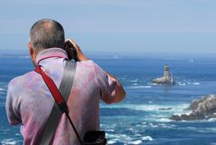 Photographer behind the sea. And a lighthouse Stock Image