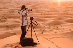 Photographer behind tripod on sand dune is silhouetted by settin Stock Image