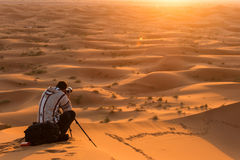 Photographer behind tripod on sand dune is silhouetted by settin Stock Photography