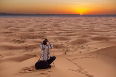 Photographer behind tripod on sand dune is silhouetted by settin Stock Images