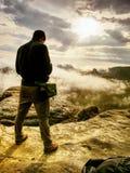 Photographer check display of camera. Man stay on cliff. Photographer bend head check display of camera. Man stay on cliff and takes photos. Autumn beautiful stock photos