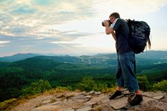 Photographer with big mirror camera on neck and backpack stay on peak of rock. Hilly landscape, fresh green color in valley. Stock Images