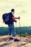 Photographer with big mirror camera on neck and backpack stay on peak of rock. Hilly landscape, fresh green color in valley. Stock Photos