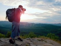 Photographer with big mirror camera on neck and backpack stay on peak of rock. Hilly landscape, fresh green color in valley. Stock Photo