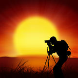 Photographer with big sun background Royalty Free Stock Photography