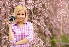 Photographer. Blonde Girl with Retro Camera over Cherry Blossom. Stock Photography