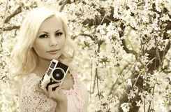 Photographer. Blonde Woman with Retro Camera over Cherry Blossom. Black and White Royalty Free Stock Image