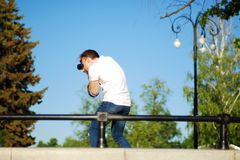 Photographer at work in city park, photo shoot in nature royalty free stock image
