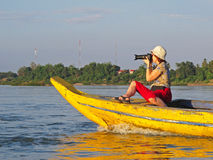 Photographer on boat. Female photographer on a boat on Mekong river. Trying to take a picture of the rare Irrawaddy river dolphins. Near the city of Kratie Stock Photo