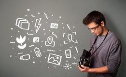 Photographer boy capturing white photography icons and symbols. Young photographer boy capturing white photography icons and symbols Stock Photography