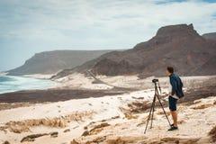 Photographer with camera in desert admitting unique landscape of sand dunes volcanic cliffs on the Atlantic coast. Baia. Das Gatas, near Calhau, Sao Vicente Royalty Free Stock Image