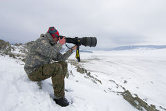 A photographer with camera enjoying snowy nature Stock Image