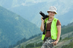 Photographer with camera in mountains Stock Image