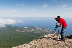 Photographer with camera on mountains. Photographer with digital camera on mountains Royalty Free Stock Photography