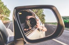 Photographer with camera reflected in the rear view mirror. Young male photographer with camera reflected in the rear view mirror of a car on the road in a Stock Images