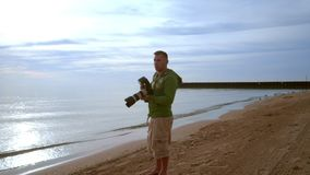 Photographer with camera on sea beach. Photographer shooting stock video footage