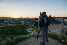 Photographer with camera at sunrise. In front of ancient castle Royalty Free Stock Photos