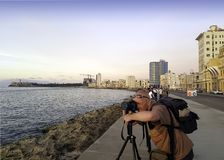 Photographer with camera during sunset in Havana, Cuba. Photographer with camera during sunset with Atlantic Ocean, residential building and Morro Castle in Royalty Free Stock Image