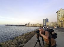 Photographer with camera during sunset in Havana, Cuba. Photographer with camera during sunset with Atlantic Ocean, residential building and Morro Castle in Royalty Free Stock Photo