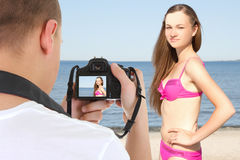 Photographer with camera taking picture of beautiful woman on th Royalty Free Stock Photography