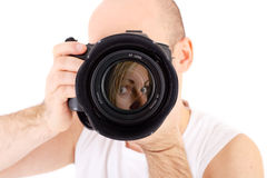 Photographer with camera taking portrait. A photographer pointing his camera on a female model (reflexion in lens) isolated on white Stock Image