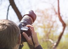Photographer with camera with telephoto lens. Shooting distant objects Stock Images