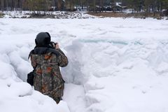 Photographer in camouflage jacket taking pictures from ambush in winter. Photographer in the camouflage jacket photographs of the village from an ambush in the royalty free stock photos