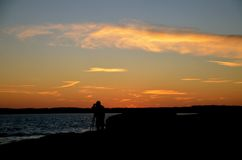 A photographer captures the Ocean as the sun sets. Near the ocean in Maine light house with the light shining on the  sea gulls are free to fly Royalty Free Stock Photo