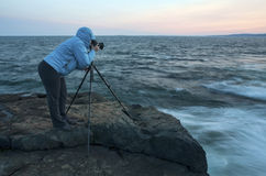Photographer capturing a sunset. A photographer using a tripod-mounted SLR camera to capture a sunset on a rocky coast Stock Photography