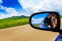 Photographer in car mirror drives near valley Stock Photos