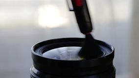 The photographer carries out cleaning of the camera lens. stock video footage