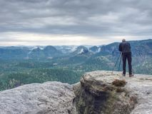 Photographer check display of camera on tripod. Man stay on cliff. And takes photos talk friends. Autumn beautiful misty landscape misty sunrise at horizon. Men royalty free stock photos