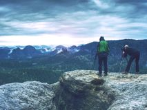 Photographer check display of camera on tripod. Man stay on cliff stock image