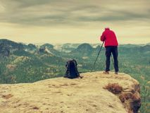 Photographer check display of camera on tripod. Man stay on cliff. And takes photos talk friends. Autumn beautiful misty landscape misty sunrise at horizon. Men royalty free stock images