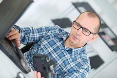 Photographer checking digital pictures on laptop indoors Stock Photography