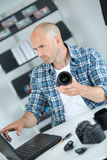 Photographer checking digital pictures on laptop in agency Stock Images