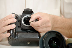 Photographer cleaning sensor of his camera Royalty Free Stock Photography
