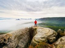 Photographer on the crater. Man on peak above thick cloud, dark rainy weather Stock Photography
